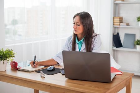 persona escribiendo: Retrato del doctor médico que trabaja en el lugar de trabajo de oficina médica por escrito prescripción sentado en el escritorio