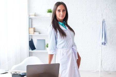 Portrait of young woman doctor with white coat standing in medical office looking at the camera