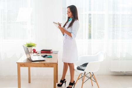bata blanca: Mujer del médico que trabaja en el consultorio médico