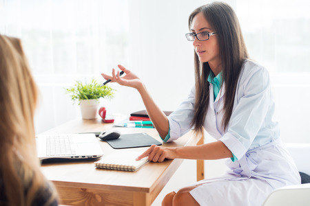Medical physician doctor woman talking to patient sitting by the table