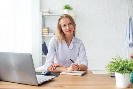 mujeres sentadas: Mujer del médico sentado en el escritorio en la oficina médica Foto de archivo