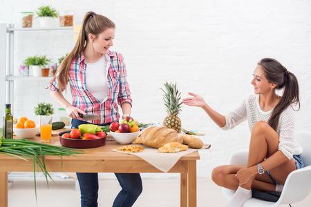 Mujer que cocina en una cocina y hablar con su concepto de amigo amistad preparación culinaria Foto de archivo - 43895758