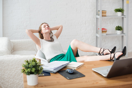 Businesswoman resting relaxing legs on the table hands behind her head and sitting on a chair in office