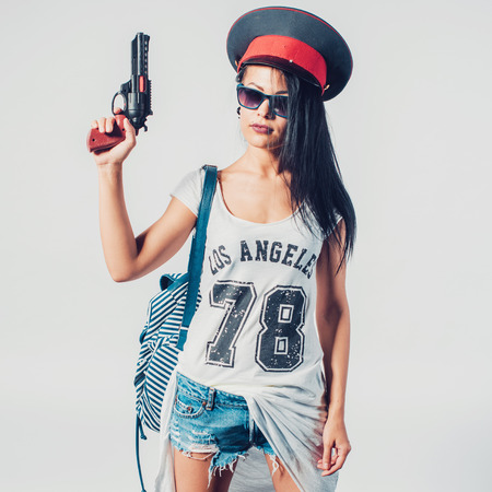 sexy police: Fashion swag sexy girl holding toy gun woman having fun wearing police cap Stock Photo