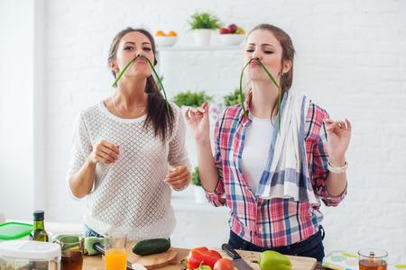 nutricion: Las mujeres preparan la comida sana jugando con verduras en la cocina que se divierte la nutrición concepto de dietas.