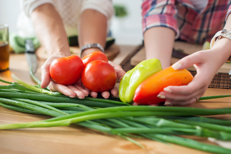 Women preparing dinner in a kitchen holding vegetables in hands concept dieting healthy food cooking at home