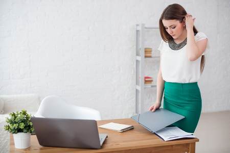 woman in office: business woman at office standing near table with documents Stock Photo