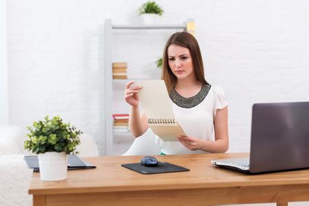 empresaria con la computadora portátil y el concepto de diario de trabajo independiente en el hogar, la planificación, la programación.
