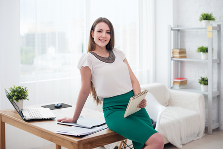 teleworker: Portait of beautiful successful business woman in office sitting on table.