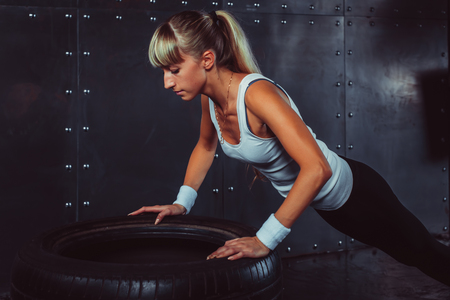 close ups: Sportswoman. Fit sporty athlete woman doing push ups on tire strength power training concept crossfit fitness workout sport and lifestyle side view close up. Stock Photo