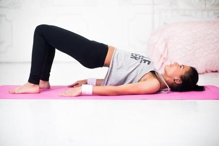 espina dorsal: Puente pose mujer deportiva haciendo el calentamiento de ejercicio para la columna vertebral, salto mortal hacia atrás, arqueando estirar su espalda que se resuelve en gimnasia para el hogar gimnasia ejercicios de yoga concepto.