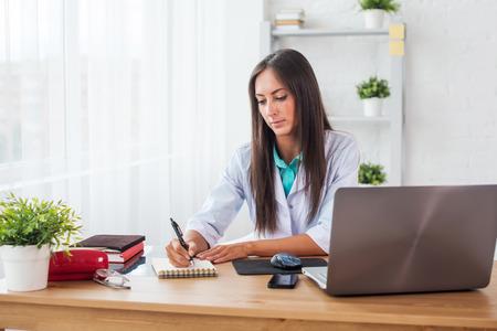 recetas medicas: Retrato del doctor médico que trabaja en el lugar de trabajo de oficina médica por escrito prescripción sentado en el escritorio