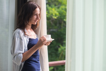 view girl: Woman in wide, long shirt is drinking tea or coffe and looking through the window.  Young lady is meeting sunrise