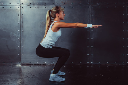 Athletic young woman fitness model warming up doing squats exercise for the buttocks concept sport slimming healthy lifestyle. Stockfoto