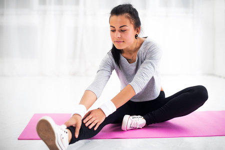 Fit woman doing aerobics gymnastics stretching exercises her leg and back to warm up at home on yoga mat
