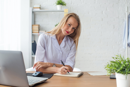 white coat: Portrait of physician working in her office writing prescription sitting workplace