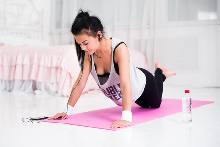 working at home: Fit sporty woman in headphones doing push ups home training listening music at smartphone concept crossfit fitness workout sport and lifestyle Stock Photo