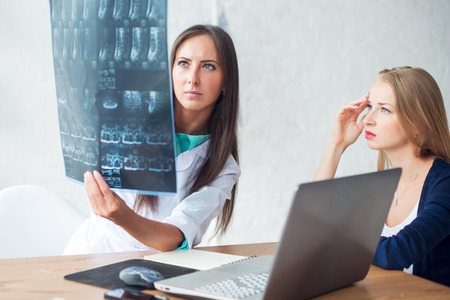 spine: doctor and patient looking at x-ray or MRI concept healthcare, medical and radiology concept Stock Photo