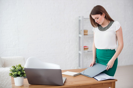 computer case: business woman at office standing near table with documents Stock Photo