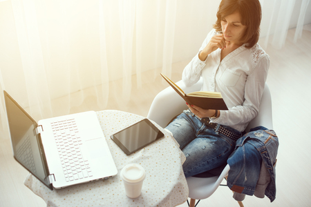teleworker: businesswoman with laptop and diary in a bright office concept freelance work at home