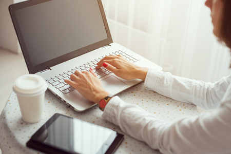 フリーランサーは、ノートブック、自宅のキーボードで入力するラップトップ コンピューターで作業する女性を使用して。