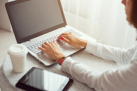 trabajando en casa: Freelancer que usa el cuaderno, la mujer que trabaja en el ordenador port�til escribiendo en el teclado en casa. Foto de archivo