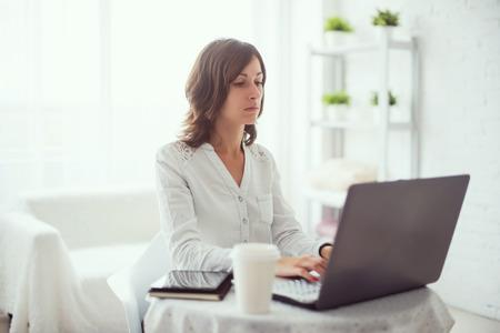 フリーランサーは、ノートブック、自宅のキーボードを入力するラップトップ コンピューターで作業する女性を使用して。