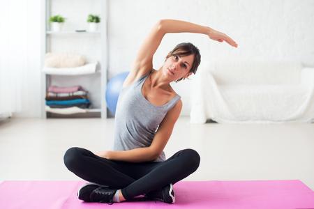 columna vertebral: Ajustar la mujer estirando su detrás ejercicio de la columna vertebral se caliente gimnasia concepto de aeróbicos en casa.