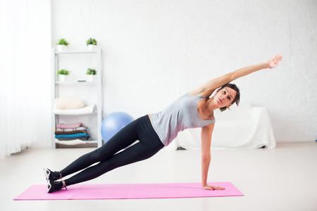 fitness: Fit vrouw die kant plank yoga stelt thuis in de woonkamer op de mat Concept pilates fitness gezonde levensstijl