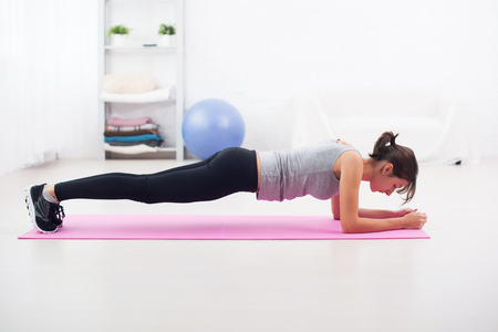 Fit girl in plank position on mat at home in the living room exercise for back spine and posture Concept pilates fitness sport