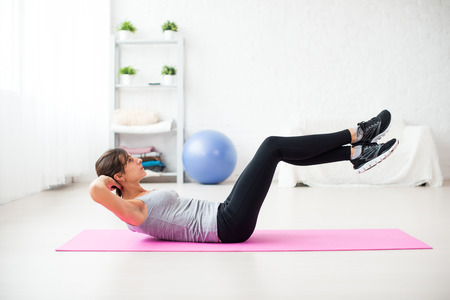 pilates studio: Woman doing abdominal crunches pilates exercise on mat at home