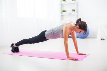 fit vrouw doet push-ups op de vloer in haar woonkamer op een oefening mat thuis