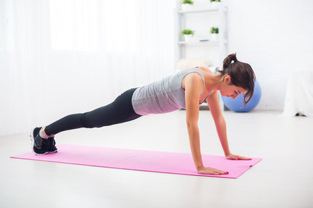 strength training: fit woman doing push-ups on the floor in her living room on an exercise mat at home