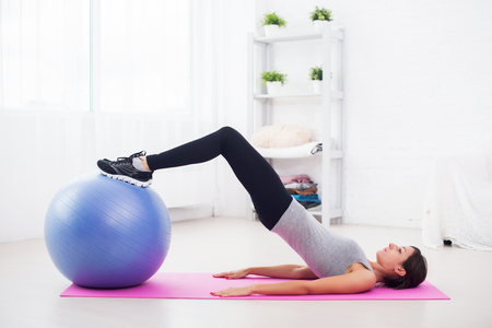 pelvis: sporty woman doing pilates exercise lifting her pelvis with fit ball at home