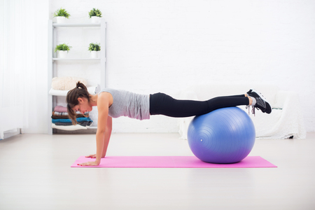 Woman doing push-ups on the floor with fit ball in her living room an exercise mat at home. Stock Photo