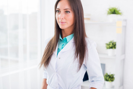 bata blanca: Portrait of young woman doctor with white coat standing in medical office