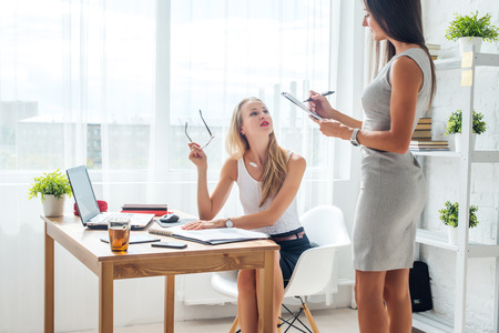 business planning: Two young woman colleague at office working standing and talking. Stock Photo