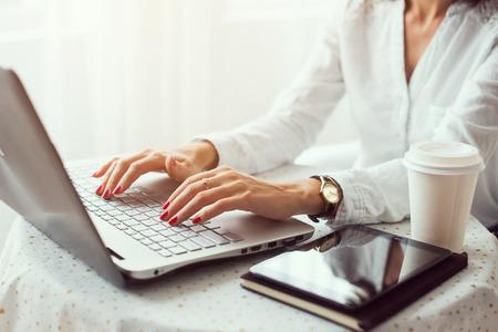 trabajando en computadora: Mujer que trabaja en la oficina en casa mano en el teclado de cerca Foto de archivo