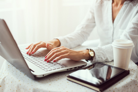 teleworking: Woman working in home office hand on keyboard close up