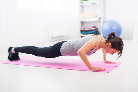 Mulher apta a fazer flexões no chão em sua sala de estar em uma esteira de exercícios em casa Imagens