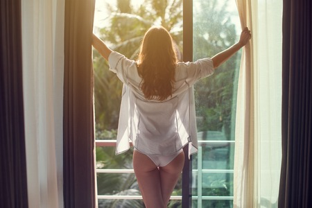 good looking model: Lovely woman is awoke and standing before window. Girl is opening curtains and meeting sunrise