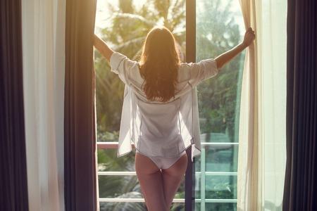 Mujer encantadora es despertó y de pie ante la ventana. La muchacha está abriendo las cortinas y el cumplimiento de la salida del sol