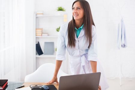 health professional: Portrait of young woman doctor with white coat standing in medical office looking at the camera