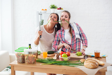 fun: Women preparing healthy food playing with vegetables in kitchen having fun concept dieting nutrition.