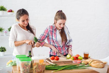 mujeres cocinando: Dos amigos de muchachas preparaba la cena en un concepto de cocina cocina, culinario, el estilo de vida saludable