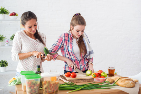 cooking ingredients: Two girls friends preparing dinner in a kitchen concept cooking, culinary, healthy lifestyle