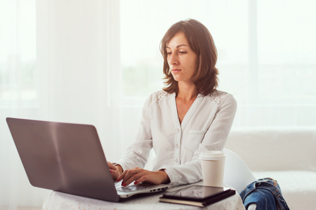 business woman working: young business woman working at desk typing on a laptop in office Stock Photo