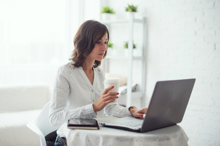 trabajando en casa: Mujer de negocios joven que trabaja en el escritorio escribiendo en un ordenador port�til en la oficina y beber caf�. Foto de archivo