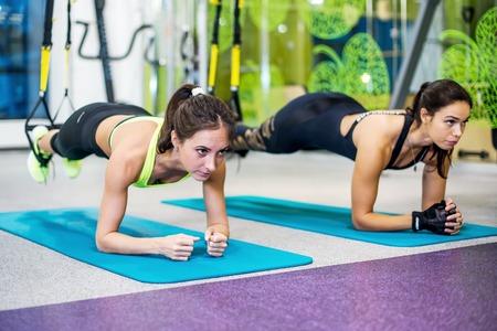 ejercicio aeróbico: Las niñas en forma en el gimnasio haciendo ejercicio tablón de espina dorsal y la postura del concepto de deporte de aptitud pilates