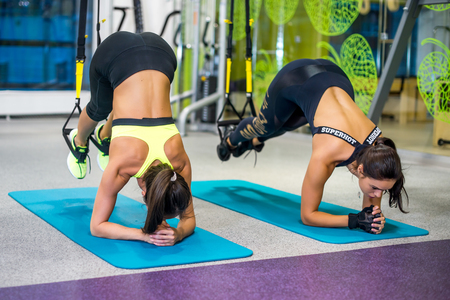 Woman exercising with suspension straps in fitness club or gym Stok Fotoğraf